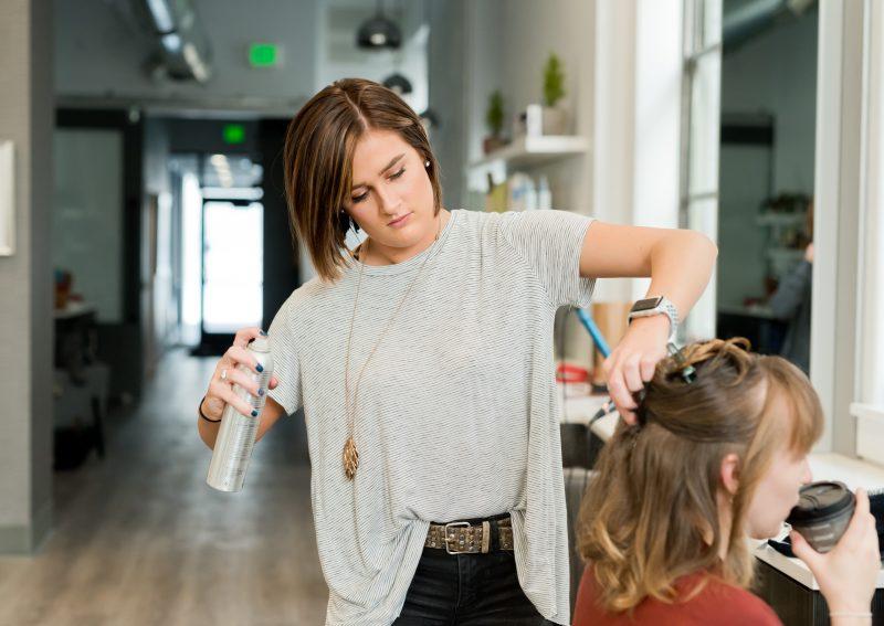 Hairdresser spraying customer's hair in a hair salon