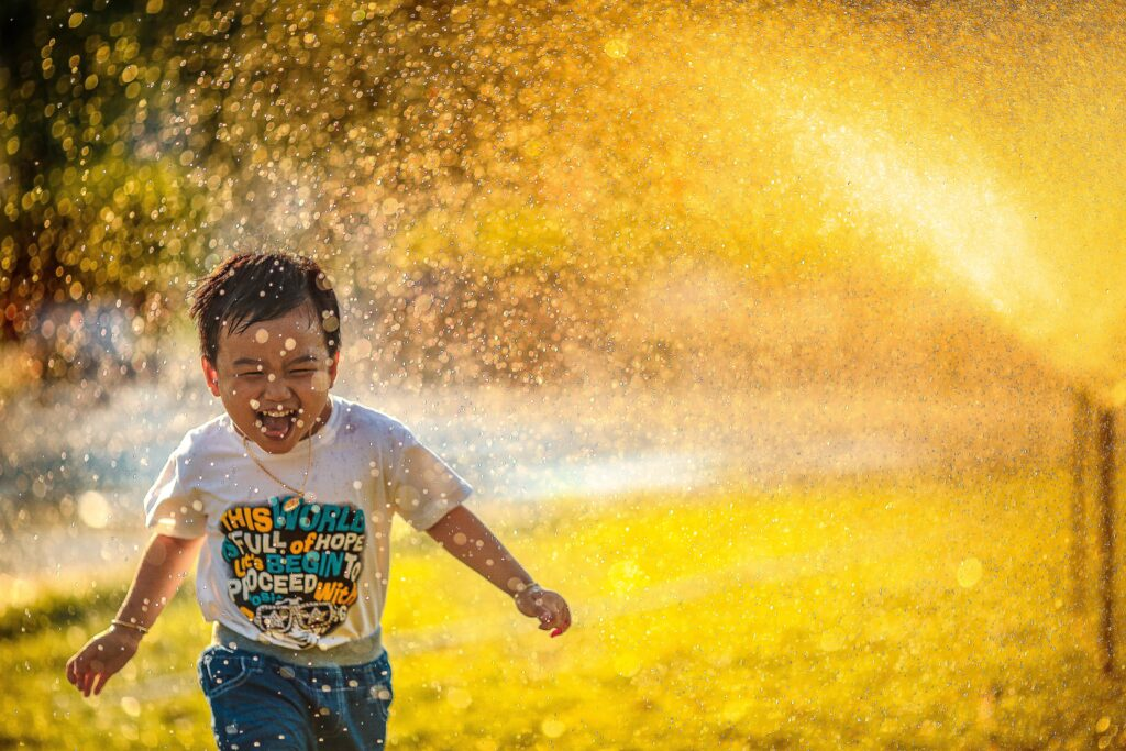 An image of a child running through a water sprinkler.